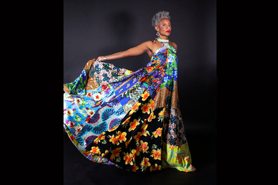 Dance professor Cynthia Oliver holding out the skirt of her colorful, full-length dress.