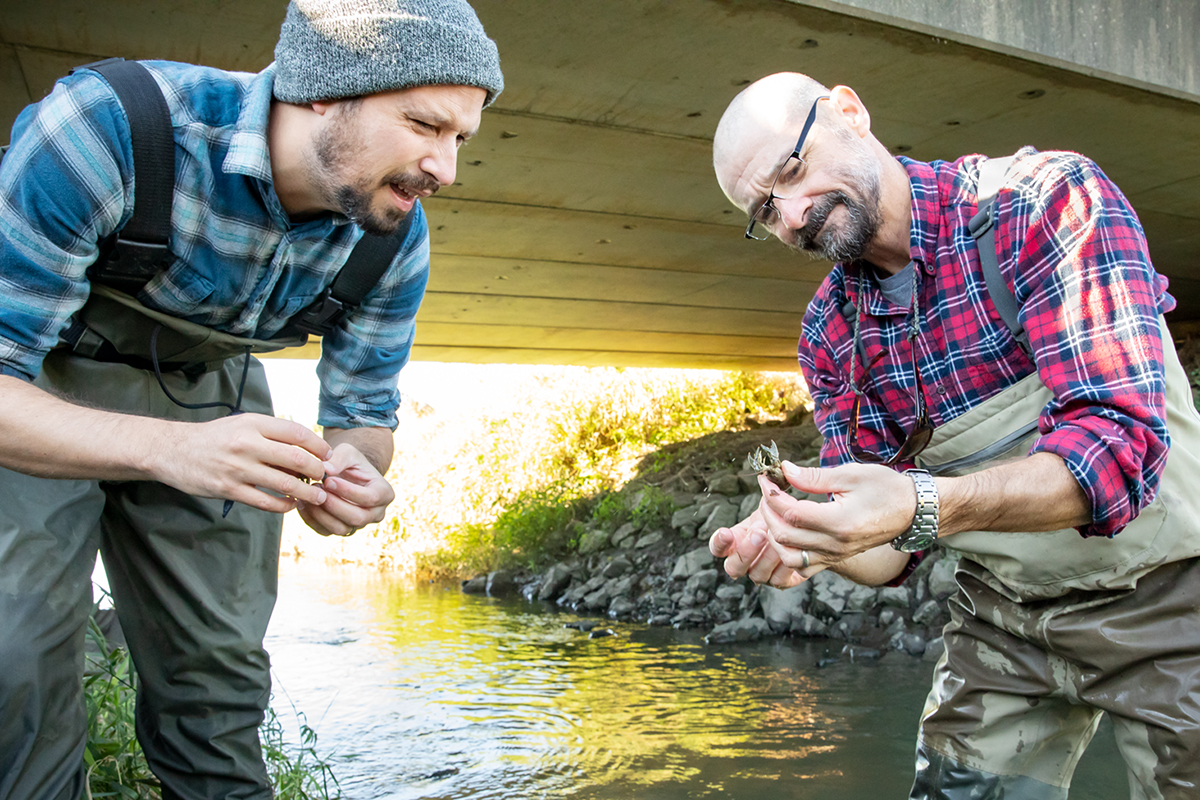 Eric Larson, left, and Christopher Taylor inspect a captured crayfish.