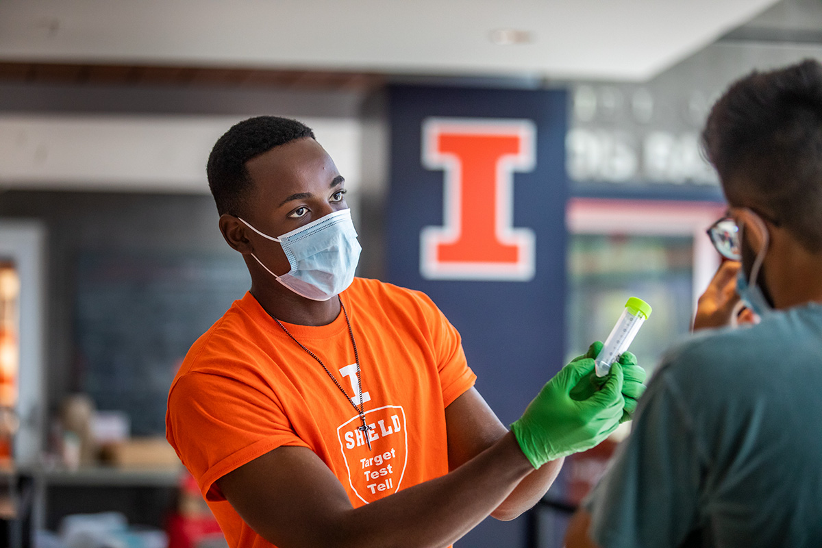 A SHIELD worker explains the protocol for a COVID-19 saliva test at the University of Illinois.
