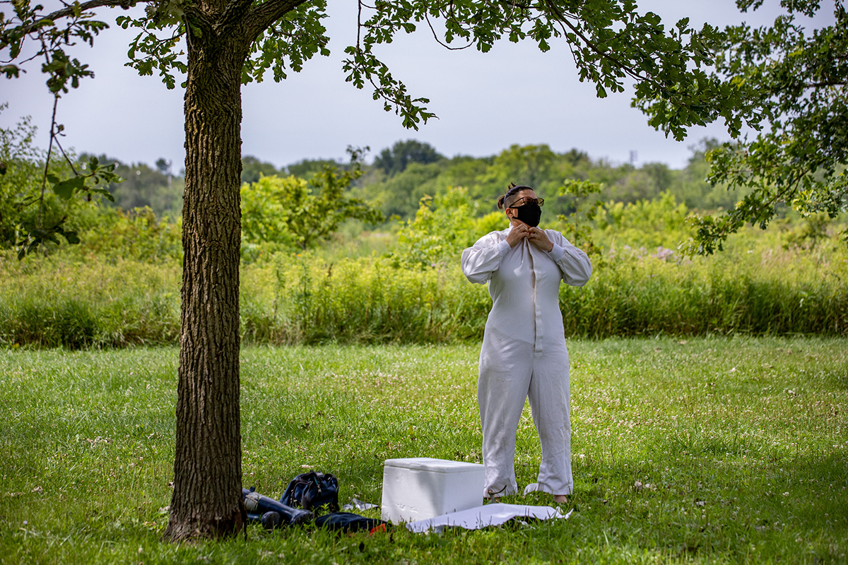 Vector ecologist Holly Tuten stands under a tree and buttons up her white coveralls.