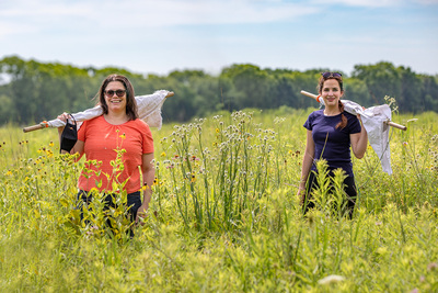 Holly Tuten and graduate student Erica Hernandez stand in a prairie with drag cloths attached to poles over their shoulders. They are smiling and looking at the camera.