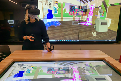 Art professor Chiara Vincenzi wearing virtual reality goggles and standing in front of a screen displaying dresses in a virtual world.