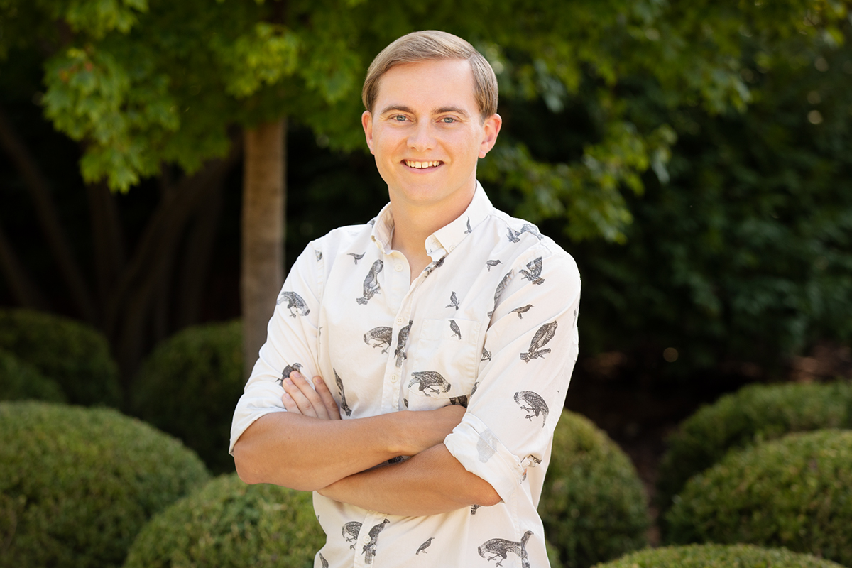 Ph.D. student Nicholas Antonson stands outdoors with his arms crossed. He is smiling.