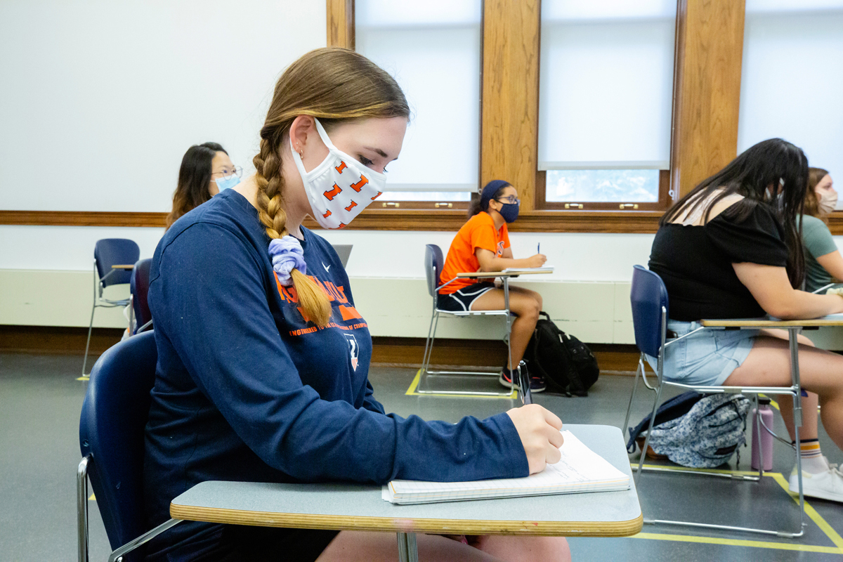 Female student in classroom with face covering taking notes.