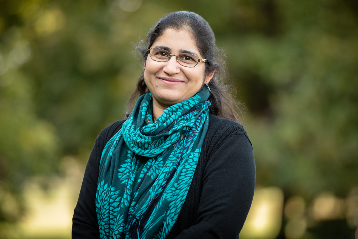 Professor Sumiti Vinayak stands outdoors, wearing a black sweater and a blue scarf.