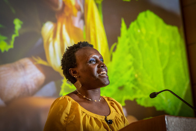 Ngumbi speaks at a podium with an image of a flowering plant projected behind her.