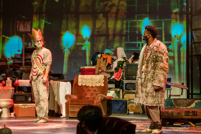 A white man in a gold crown, sash and filthy white pants and a black man in a furry coat stare at each other on stage in front of an armchair and piles of garbage.