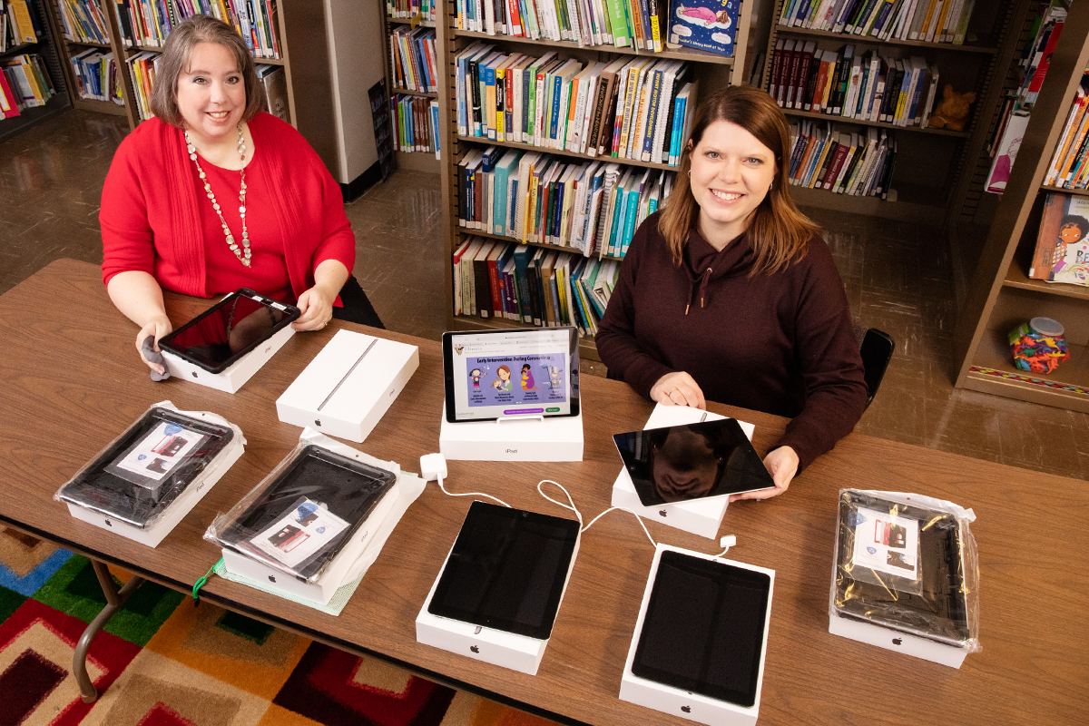 Librarian Sarah Isaacs and research information specialist Jill Tompkins sitting at a table with tablet computers and Wi-Fi hotspots on it.