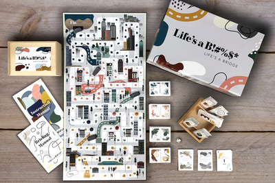 Image of a board game with cards, instruction manual and dice
