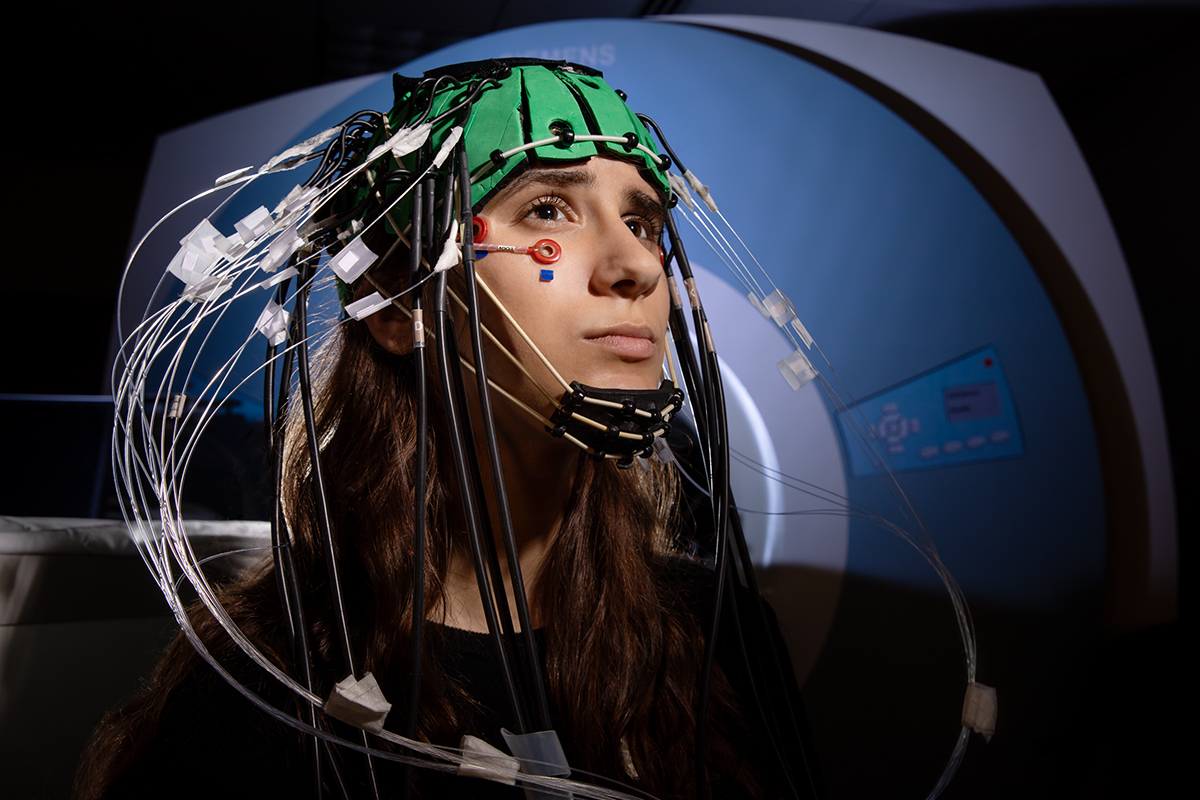Photo of a young woman inside an MRI suite wearing an imaging cap with many sensors attached.