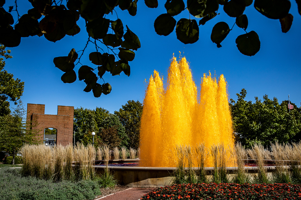 Bright orange water sprays into a blue sky during the Homecoming kickoff celebration.