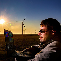 Photo of student staring at computer screen with wind turbines in the background.