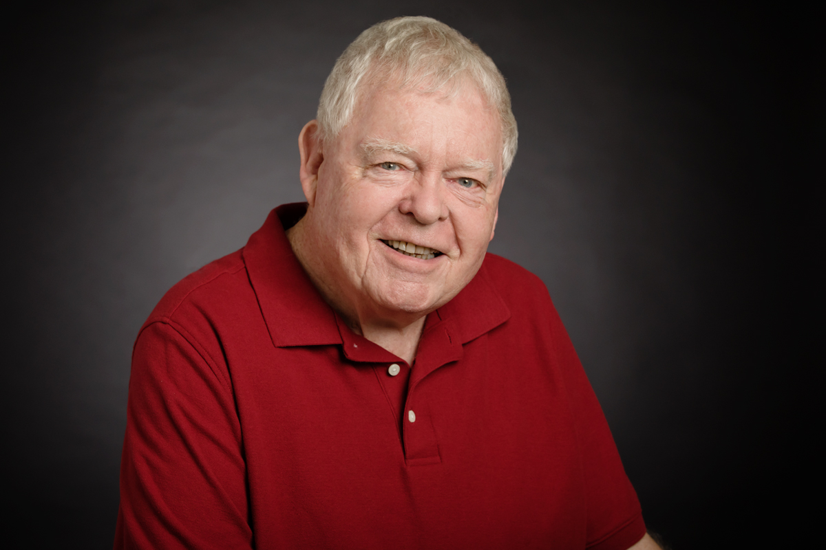 Portrait of Thomas O'Rourke. He is wearing a dark red shirt and smiling.