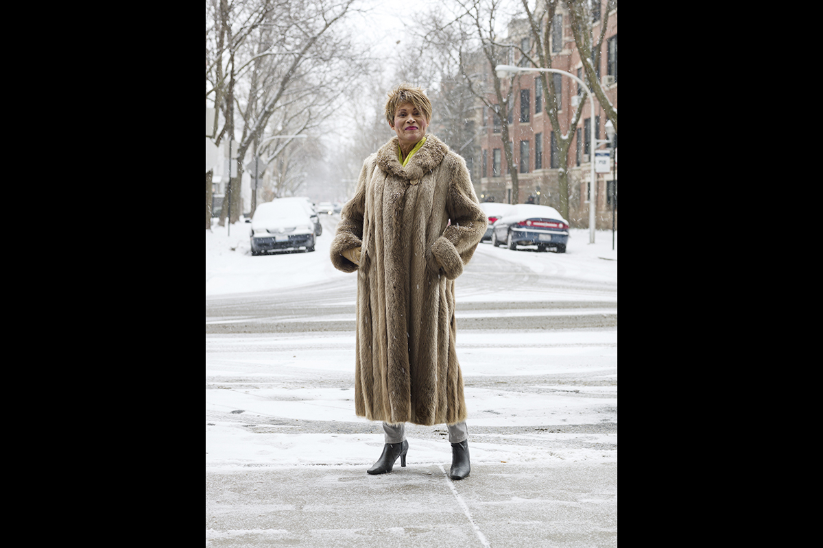 Photo of Gloria Allen standing in a full-length fur coat on a snowy street.