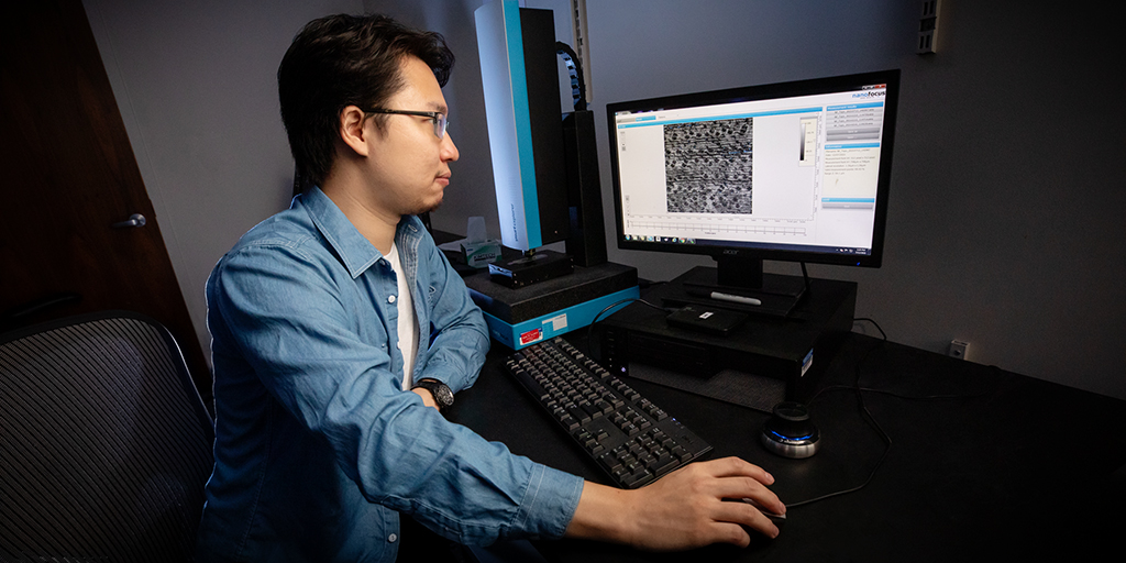 The researcher looks at a computer monitor with a microscopic image of a plant epidermis.