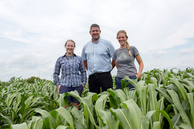 Photo of three researchers standing in a field of sorghum.