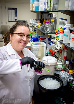 Photo of researcher in her laboratory. She is holding a test tube of green chloroplasts over a bucket of ice. Behind her are shelves full of laboratory equipment and supplies