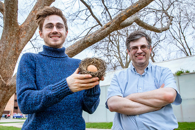 Portrait of the researchers outside. Daniel Clark is holding a nest and egg.