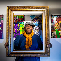 Stacey Robinson holding a frame around his face, with his artwork on the wall behind him.