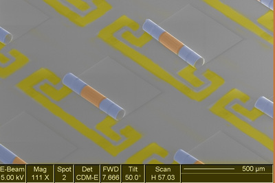 Electron microscope image of an array of new chip components that integrate the inductors, blue, and capacitors, yellow, needed to make the electronic signal filters in phones and other wireless devices.