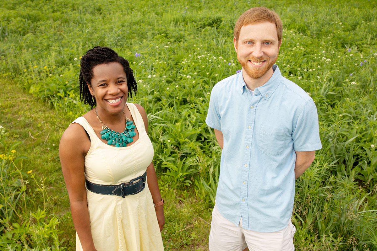 Researchers stand in a natural area with prairie plants in the background.