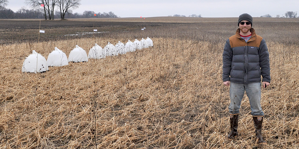 Clem stands near one of the field sites with a row of tiny white tents in the background.