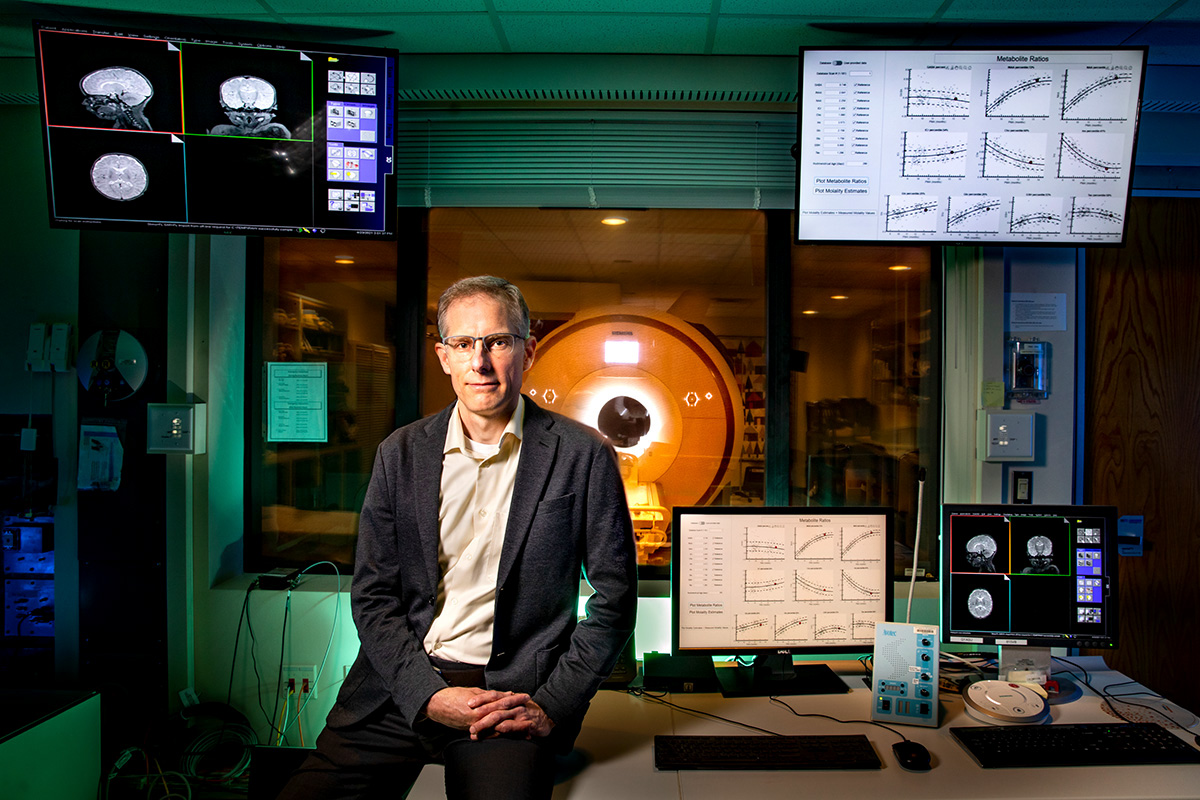 Researcher sits on a desk with readouts on computer monitors surrounding him and a magnetic resonance imaging device in the background.