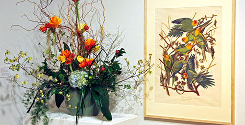 The colors in a painting of parakeets inspired this floral arrangement at the 2009 Petals & Paintings exhibition at Krannert Art Museum.