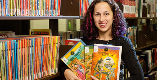 South Asian Studies librarian Mara Thacker holds some of the comics from the Undergraduate Library's collection of Indian comic books.