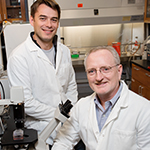 Professor of pathobiology Daniel Rock (seated) and postdoctoral researcher Diego Diel are part of a team that will work to create a one-dose vaccine for livestock that will prevent multiple diseases for an extended period of time.