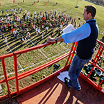 Band director Barry Houser supervises the Marching Illini from a rented scissor lift overlooking the field behind the Krannert Art Museum.