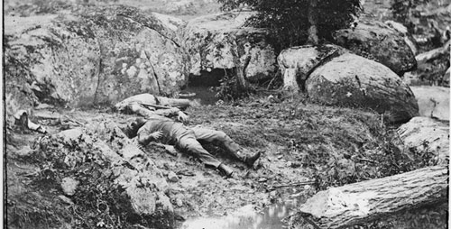"Photos of the carnage from Gettysburg and other Civil War battles shocked many who saw them, but also provided a way to manage grief and trauma, says communication professor Cara Finnegan. At left, dead Confederate soldiers in the ""slaughter pen"" at the foot of Little Round Top at Gettysburg."