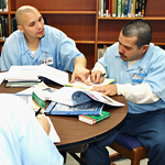 EJP student Rafael Cortez, left, helps fellow prisoner Victor Quintero learn English.