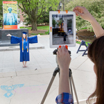 The augmented reality Alma Mater mobile app offered students many now-you-see-it, now-you-don't moments. Here, history and communication graduate Madeline Ley poses in front of the pedestal with a poster of Alma, which triggered the mobile app to insert a 3-D image of the Alma Mater sculpture.