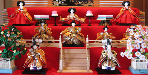Hina dolls are presented in a carefully arranged display, with dolls representing the Emperor and Empress, court attendants, musicians, ministers and samurai.