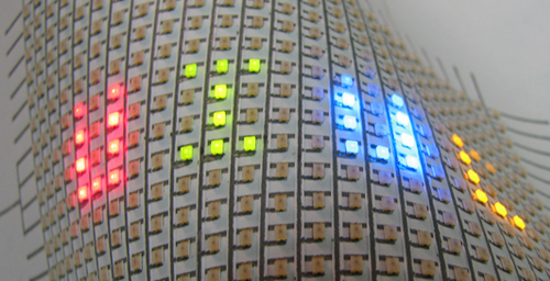 A flexible array of LEDs mounted on paper. Hand-drawn silver ink lines form the interconnects between the LEDs.