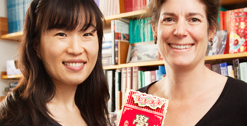 Psychology professor Eva Pomerantz, right, student Lili Qin and their colleagues found that American children's sense of obligation to their parents and desire to please them by doing well in school declined in the seventh and eighth grades, while Chinese students of the same age generally maintained their feelings of obligation and increased their motivation to please their parents with their academic achievements. Qin holds a Chinese greeting card offering the recipient good luck with academics in the new year.