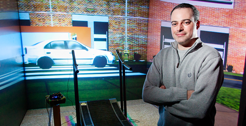 Postdoctoral researcher and study co-author Mark Neider in the lab with the multidirectional treadmill and simulated street scene used in the multi-tasking study.