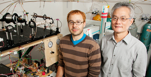 A study led by University of Illinois plant biology professor Feng Sheng Hu (right), with graduate student Michael Urban, used a spooling-wire micro-combustion device (pictured) coupled with an isotope mass spectrometer to analyze individual grains of grass pollen to determine the age of C4 grasses. The study pushed back the origin of C4 plants by millions of years.