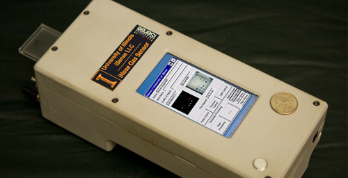 The handheld reader analyzes the color changes in the sensor array to quickly monitor the environment for explosive chemicals.