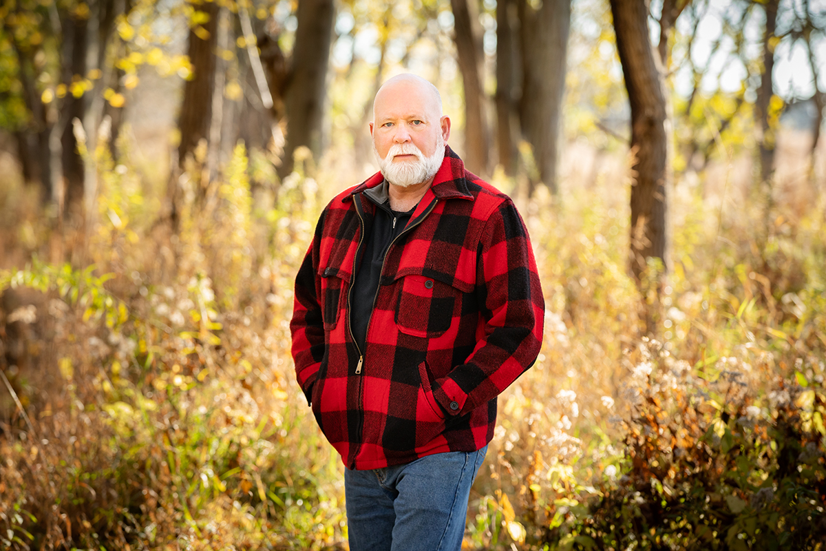 Craig Miller stands in the woods facing the camera. He is wearing a red and black plaid shirt and he has his hands in his pockets.