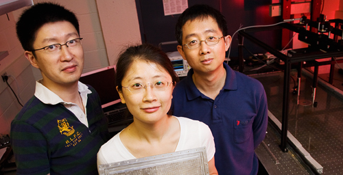 "A team of Illinois researchers led by Nicholas X. Fang, left, a professor of mechanical science and engineering, has created the world's first acoustic ""superlens."" Doctoral student Shu Zhang holding the lens and Leilei Yin, a microscopist at Beckman Institute, were co-authors."
