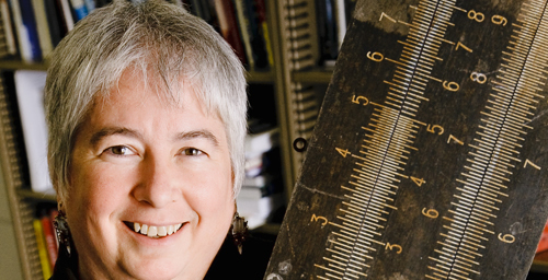 Lori Kendall, a professor in the Graduate School of Library and Information Science, says despite the increased popularity of geek culture and the ubiquity of computers, the geek's close cousin, the nerd, still suffers from a negative stereotype in popular culture. Kendall holds a familiar tool of the nerd: a slide rule.