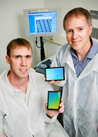 Paul Hergenrother, left, professor of chemistry, and Brian Cunningham, professor of electrical and computer engineering, hold biosensors they've developed that are capable of detecting protein-DNA interactions.