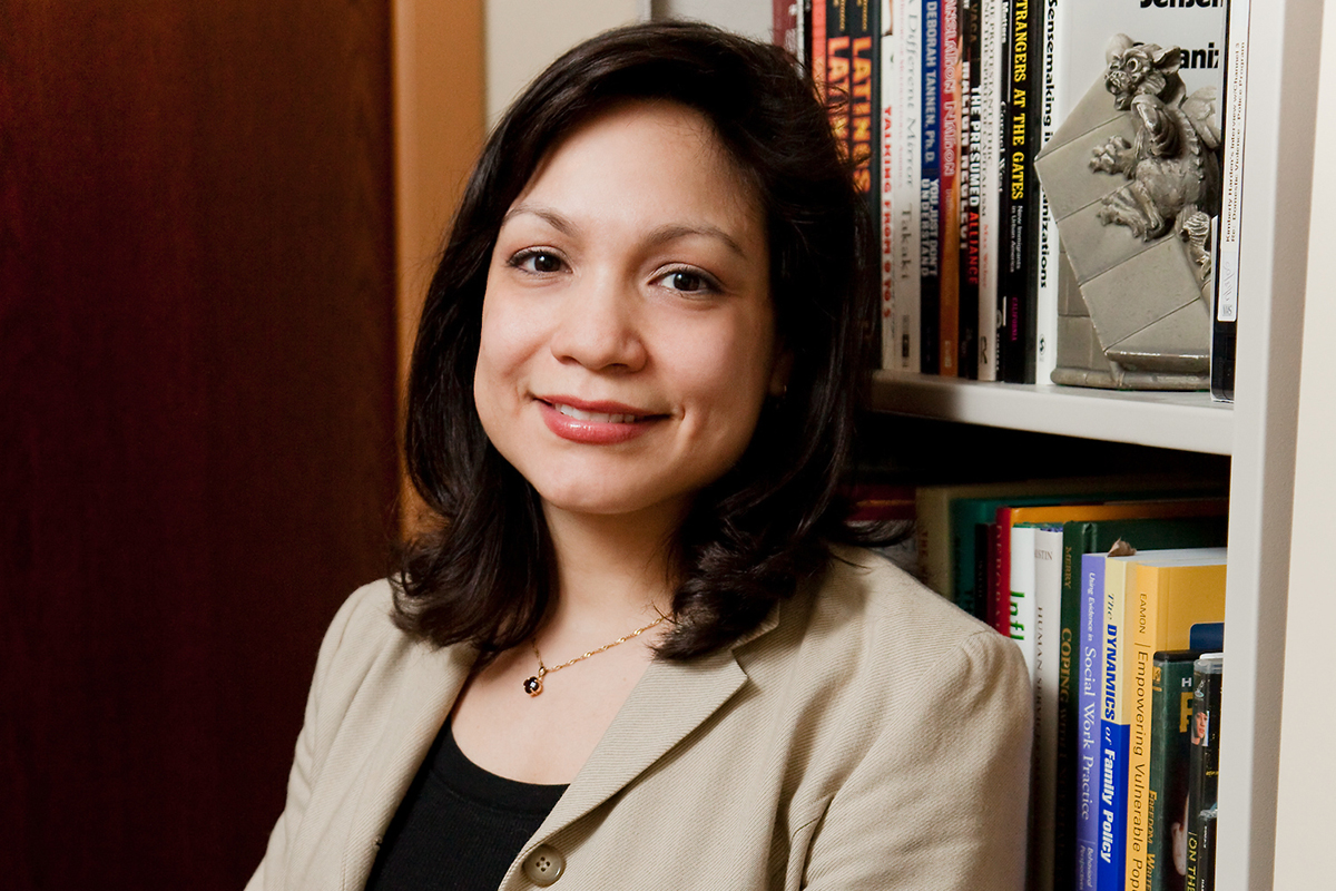 Photo of U. of I. social work professor Lissette Piedra leaning against a bookcase in her office