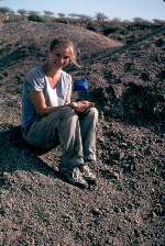 Leslea Hlusko, professor of anthropology, holds the fossil toe bone that she uncovered where the blue flag is in the ground near her in Ethiopia. The toe bone was among several fossils belonging to the earliest known human ancestor.