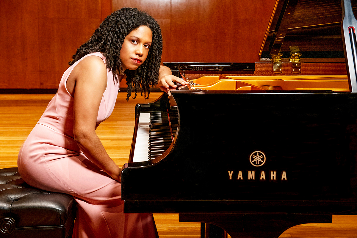Photo of Rochelle Sennet in a pink evening dress leaning over the keyboard of a Yamaha grand piano.