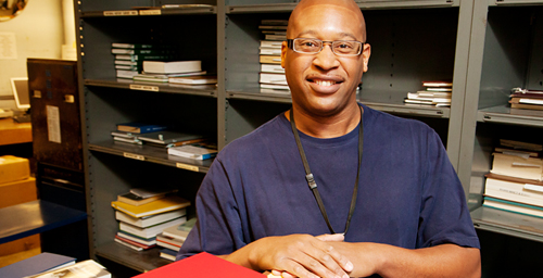 """Unbound enthusiasm Norris Purdy, a 10-year employee in the U. of I. Library's shipping and receiving division, is known for the smile on his face as much as the quality work he performs. Purdy, a recent recipient of the Chancellor's Distinguished Staff Award, is responsible for receiving, sorting and delivery of books and materials throughout the University Library system. """"We get to see some pretty rare things,"""" he said.  Click photo to enlarge"""