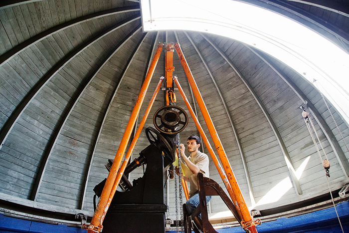 Yousef Ahessi, a sophomore engineering student at Swarthmore College, secures a portion of the U. of I. Observatory's 117-year-old telescope before it is lifted out by crane and sent to Ray Museum Studios in Pennsylvania. The telescope will undergo maintenance and renovation. It is expected to be back on campus this fall.