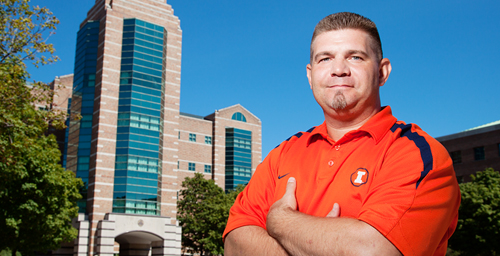 """Jason Hatton stands in front of the Beckman Institute Building, where he serves as facility manager. He said the building's architectural uniqueness had stood out to him even before he became a UI employee. """"I've always thought it looks impressive, and the tower is the perfect centerpiece for this part of campus.""""  Click photo to enlarge"""